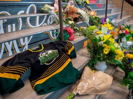 A memorial at the stairs that lead to Elgar Petersen Arena is shown in Humboldt, Saskatchewan, on Saturday, April 7, 2018. Royal Canadian Mounted Police say 14 people are dead and others injured Friday after a truck collided with a bus carrying a junior hockey team to a playoff game in northeastern Saskatchewan. Police say there were 28 people including the driver on board the Humboldt Broncos bus when the crash occurred at around 5 p.m. on Highway 35 north of Tisdale. (Liam Richards/The Canadian Press via AP) ORG XMIT: LDR147