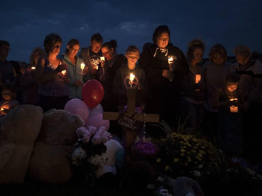 Mourners gather in front of a memorial for a candle-lit vigil for Shanann Watts and her two daughters, Bella, 4, and Celeste, 3, in front of the Watts' home on Friday, Aug. 17, 2018, in Frederick, Colo. Authorities are expected to file formal charges Monday against Christopher Watts, an oil and gas worker who authorities said dumped his wife and daughters' bodies on his employer's property. (Timothy Hurst/The Coloradoan via AP)