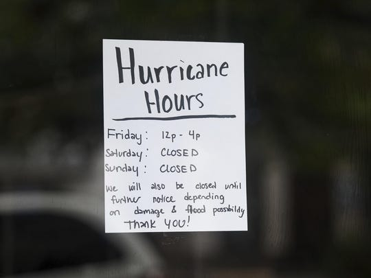 """In this Sept. 15 photo, a special announcement for """"Hurricane Hours"""" is displayed on a shop window as the remnants of Hurricane Florence slowly moved across the East Coast in Columbia, S.C."""