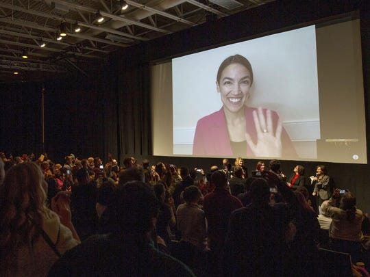 "Rep. Alexandria Ocasio-Cortez, D-N.Y. waves as she appears on screen via video conference for a question and answer session after the premiere screening of the documentary ""Knock Down the House"" during the 2019 Sundance Film Festival in Park City, Utah."