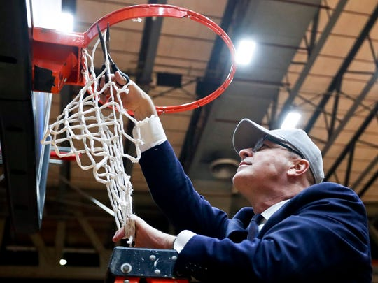Fairleigh Dickinson head coach Greg Herenda cuts down the net after his team beat St. Francis Pa. in an NCAA college basketball game for the championship of the Northeast Conference men's tournament, Tuesday, March 12, 2019, in Pittsburgh. Fairleigh Dickinson won 85-76. (AP Photo/Keith Srakocic)