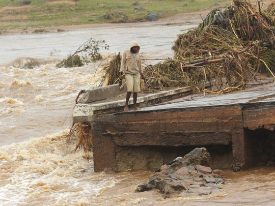 A man stands on the edge of a collapsed bridge in Chimanimani,