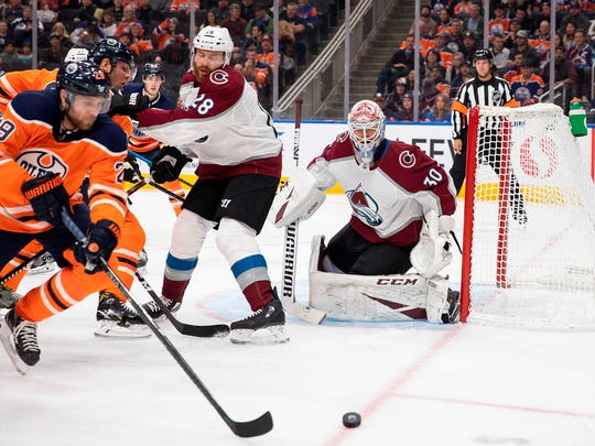Edmonton Oilers' Leon Draisaitl (29) looksto shoot against Colorado Avalanche goaltender Adam Werner (30) during second-period NHL hockey game in Edmonton, Alberta, Thursday, Nov. 14, 2019. (Codie McLachlan/The Canadian Press via AP)
