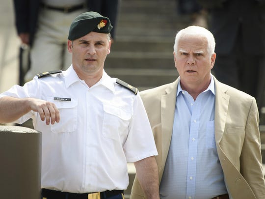 FILE - In this June 27, 2019, filke photo. Maj. Mathew Golsteyn, a former Army Special Forces soldier, leaves the Fort Bragg courtroom facility with his civilian lawyer, Phillip Stackhouse, right, after an arraignment hearing. President Donald Trump has pardoned a former U.S. Army commando set to stand trial next year in the killing of a suspected Afghan bomb-maker and for a former Army lieutenant who had been convicted of murder after he ordered his men to fire upon three Afghans, killing two, the White House announced late Friday. (Andrew Craft/The Fayetteville Observer via AP)