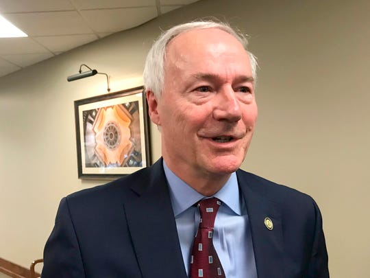 Arkansas Gov. Asa Hutchinson speaks to reporters in Little Rock on Monday after speaking to a legislative committee about his decision to continue accepting new refugees.