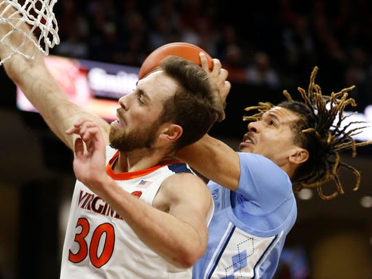 RETRANSMISSION TO CORRECT CITY - Virginia forward Jay Huff (30) and North Carolina guard Cole Anthony, right, collide under the basket during the first half of an NCAA college basketball game in Charlottesville, Va., Sunday, Dec. 8, 2019. (AP Photo/Steve Helber)