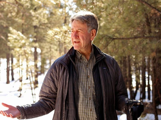 Wally Covington stands among trees in an experimental forest restoration area near Flagstaff, Ariz. Covington retired in late January as executive director of Northern Arizona University's Ecological Restoration Institute, which he founded.