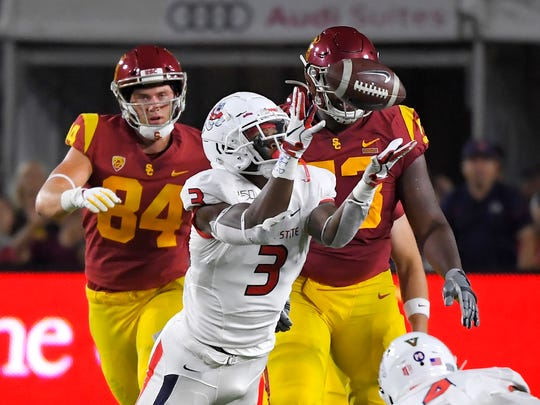 Fresno State linebacker Mykal Walker, center, almost intercepts a pass as Southern California tight end Erik Krommenhoek, left, and offensive tackle Drew Richmond watch during the first half of an NCAA college football game Saturday, Aug. 31, 2019, in Los Angeles. Walker dropped the ball after colliding with another player. (AP Photo/Mark J. Terrill)
