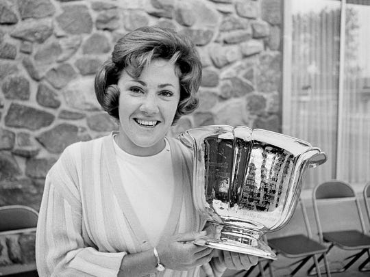 In this June 14, 1965, file photo, Susie Maxwell holds the silver trophy after winning the 36th annual Women's Western golf tournament in Chicago. Susie Maxwell Berning, one of six women to capture the U.S. Women's Open at least three times, was been elected to the World Golf Hall of Fame.