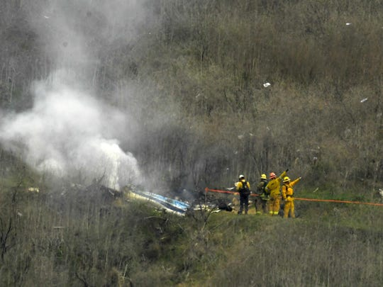 In this Jan. 26, 2020 photo, firefighters work the scene of a helicopter crash where former NBA basketball star Kobe Bryant died in Calabasas, Calif.