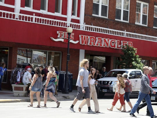 """People walk outside during a """"Summertime On The Streets"""" event that drew hundreds to downtown Cheyenne, Wyo., on June 19. The event raised concerns that people who were not wearing masks could worsen a spike in coronavirus cases."""