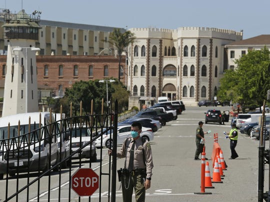 A correctional officer closes the main gate at San Quentin State Prison in California, where a second inmate on death row died from what appears to be complications of the novel coronavirus amid an outbreak sweeping through the prison.