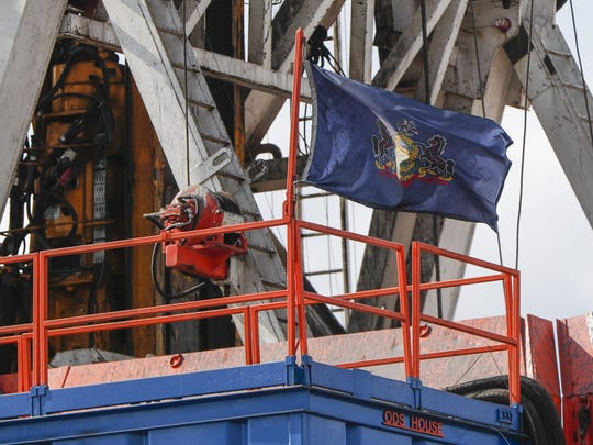 In this file photo from March 12, 2020, the flag of the Commonwealth of Pennsylvania flies on the drilling rig as work continues at a shale gas well drilling site in St. Mary's, Pa. Pennsylvania attorney general Josh Shapiro is scheduled to release results on Thursday June 25, 2020 of a grand jury investigation into natural gas hydraulic fracturing. The fracking process has raised environmental concerns while turning the state into a major energy producer.