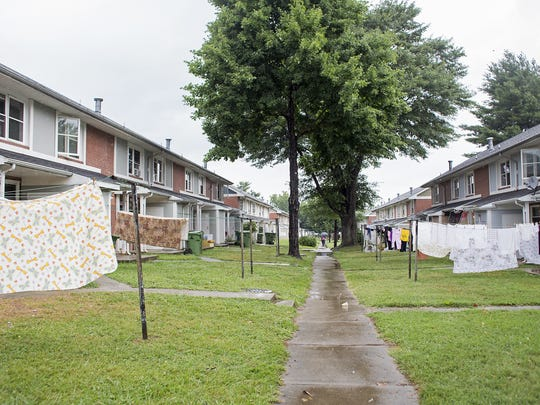 A resident walks in the rain in between rows of houses and wet hanging clothes at Hillcrest Apartments in Asheville.