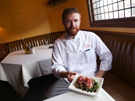 Executive Chef Damien Sutton holds a plate of goat cheese bruschetta inside of Lampy's Mediterranean Grill in Endicott in 2015.