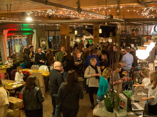 Guests drink wine and sample cheese and chocolate during the 2014 Indulge event at West End Architectural Salvage in Des Moines.