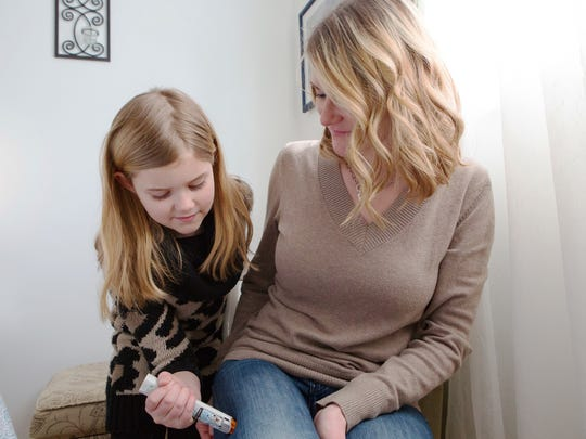 Amber Williams, a registered nurse, and her daughter Sienna, 8, give a demonstration on how to properly use an EpiPen on Feb. 28, 2015 at their home in Castle Shannon, Pa. An Epinephrine injection opens the airways for 15 to 20 minutes, long enough to get her to the emergency room.