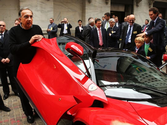 Fiat Chrysler Automobiles CEO Sergio Marchionne shows off a Ferrari after ringing the New York Stock Exchange closing bell.