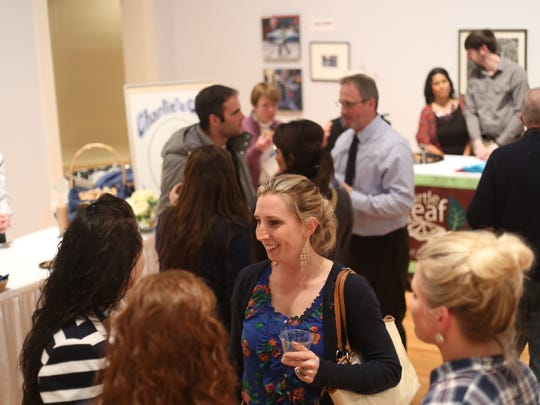 Attendees of the sixth annual Taste of Downtown at the Arnot Art Museum mingle inside the main gallery on Thursday.