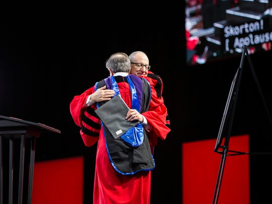 Cornell Chairman of the Board Robert Harrison hugs the school's President David Skorton during the Charter Day Ceremony which celebrated the 150th year in Cornell's history at Barton Hall on Monday, April 27, 2015.