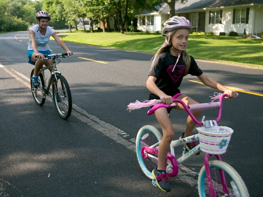 Anne Dick, left, and her daughter, Michaela, go for a bike ride with the rest of the family in Marshfield.