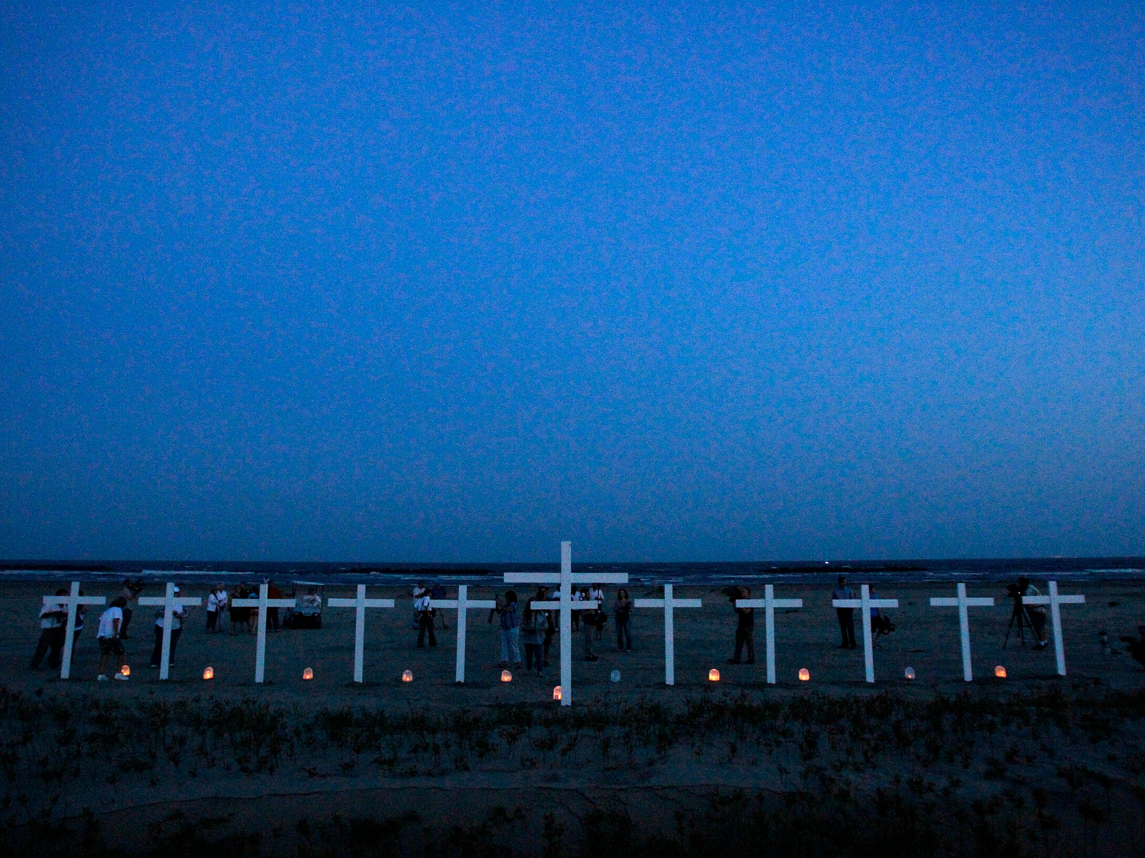 In this Wednesday, April 20, 2011 file photo, people gather at the 11 crosses erected for the workers who died in the Deepwater Horizon oil rig explosion and one for the Gulf of Mexico, center, during a vigil to mark the first anniversary of the oil spill on a beach in Grand Isle, La.