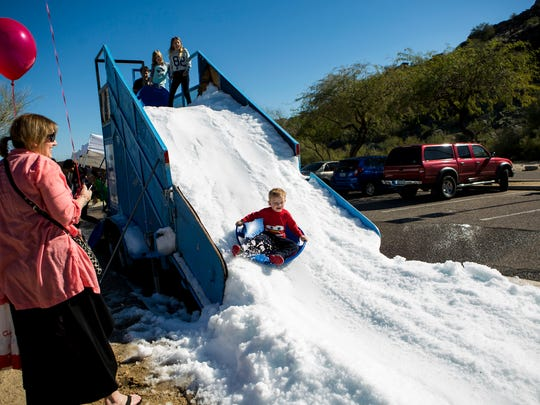 John Formanek sleds down a pile of artificial snow during the Great Canadian Picnic on Feb. 7 in Phoenix. Organizers say attendance at the event has grown in recent years.