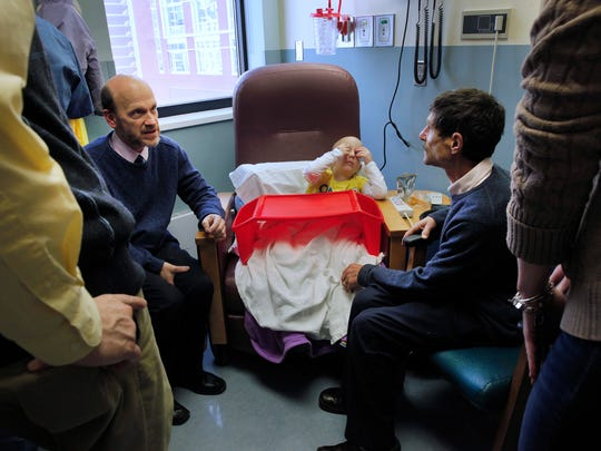 Dr. David Korones, left, and Dr. Louis Constine talk with Paul and Liz Conrow about their daughter.