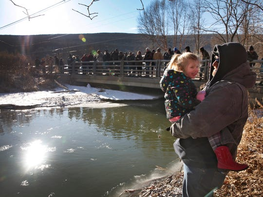 Kevin Lord holds his niece Sophie Bray, 4, as they wait to watch the annual rainbow trout sampling in Naples Creek south of Canandaigua Lake in Naples.