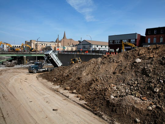 The destruction of the bridge on Broad Street, left, and the filling in of the Inner Loop, right, continues on Monday, April 6, 2015.