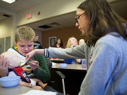 Kaydra Martin, 12, helps Franklin Jones, 12, spoon feed a fake baby in a babysitting course at the Prince St. Red Cross location on April 1, 2015.