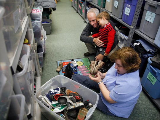 Saint's Place Clothing Closet volunteer Rose McMahon, right, helps Cuban refugees Sergio Hernandez Morales and his son Miguel Hernandez Rodriguez try on shoes in their store, which is in the Parish Center of St. John of Rochester Church in Perinton.