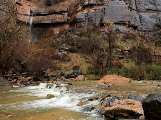 The Virgin River flows past a rain-fed waterfall Monday at the Temple of Sinawava in Zion National Park.