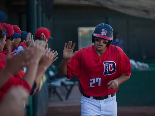 Dixie State's Kevin Kline is congratulated by teammates after scoring against Fresno Pacific at Bruce Hurst Field on Friday, May 2, 2014.