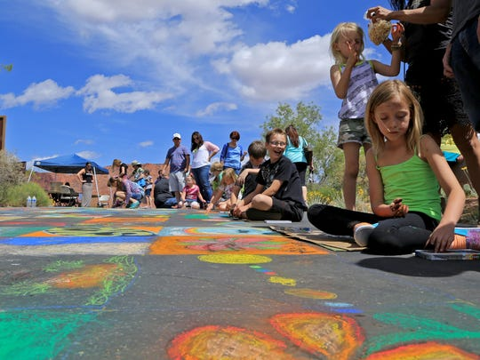 Kids try their hands at some chalk art during the 2014 Kayenta Street Painting Festival at Coyote Gulch Art Village in Ivins City.