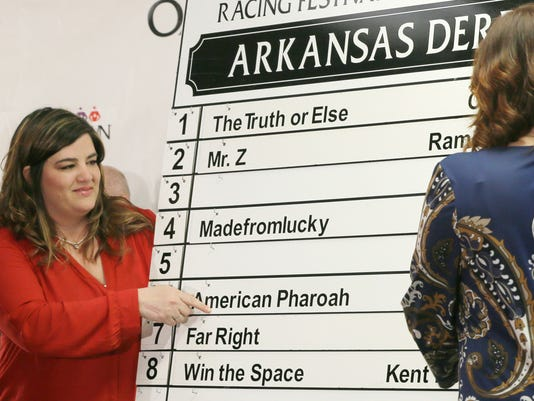 Sara Jeffers, left, and Hilari Burns place the name of thoroughbred American Pharoah in the sixth position in the post position draw for Saturday's running of the $1 million Arkansas Derby horse race at Oaklawn Park in Hot Springs, Ark., Wednesday, April 8, 2015. (AP Photo/Danny Johnston)