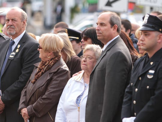Josephine Paige, center, stands with her son Michael, at the site of a memorial honoring her husband, Brinks Guard Peter Paige and two Nyack Police officers, Sgt. Edward O'Grady and P.O. Waverly Brown, as hundreds gather for the 33rd annual Brinks Memorial Service in Nyack Oct.  20, 2014.