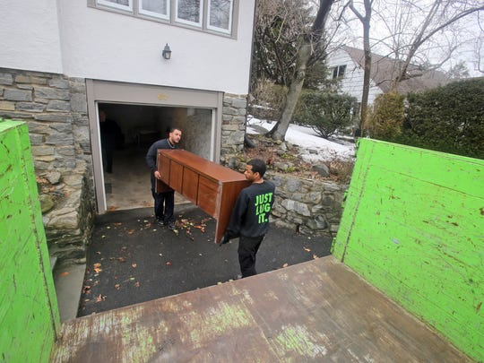 Aurelio Colon and Marshal Toone of The Junk Luggers remove an old piece of furniture from a home in Scarsdale March 17, 2015. The homeowners had hired the company to remove items no longer wanted from their home.