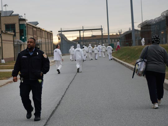 A correctional officer walks past inmates at James T. Vaughn Correctional Center as they move between buildings.