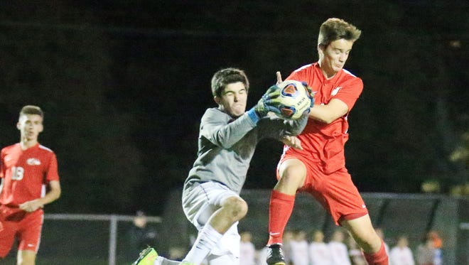 Livonia Churchill goalkeeper Adam Sinclair collides with Canton's Nick Avram while trying to snag the ball during Wednesday's first half. Sinclair was injured on the play and had to leave the Division 1 district semifinal match.