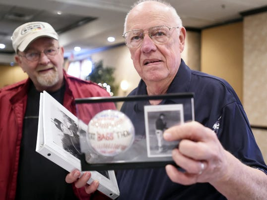 """Long-time Chambersburg baseball coach Bob Thomas, right, shows one of the gifts he received during a celebration event Saturday. Note the """"BAGS"""" written on the ball. That was the nickname used by players behind Thomas' back. Former player Ken Jones stands to the left."""