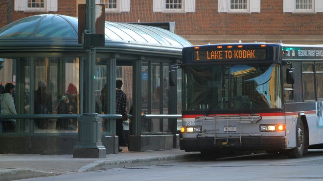 Commuters get on and off a bus along Main Street in downtown Rochester last year.