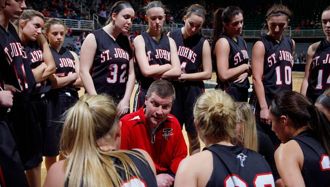 St. Johns coach Mark Lasceski talks with his team during a timeout against Detroit King during their MHSAA Class A semifinal game March 18 at the Breslin Center in East Lansing. St. Johns fell 56-48.