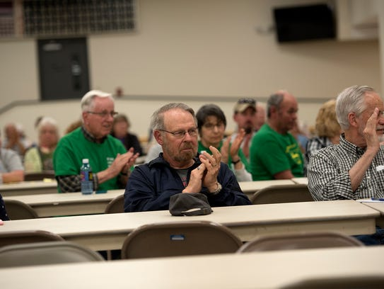 Locals opposed to Transource applaud during a hearing.