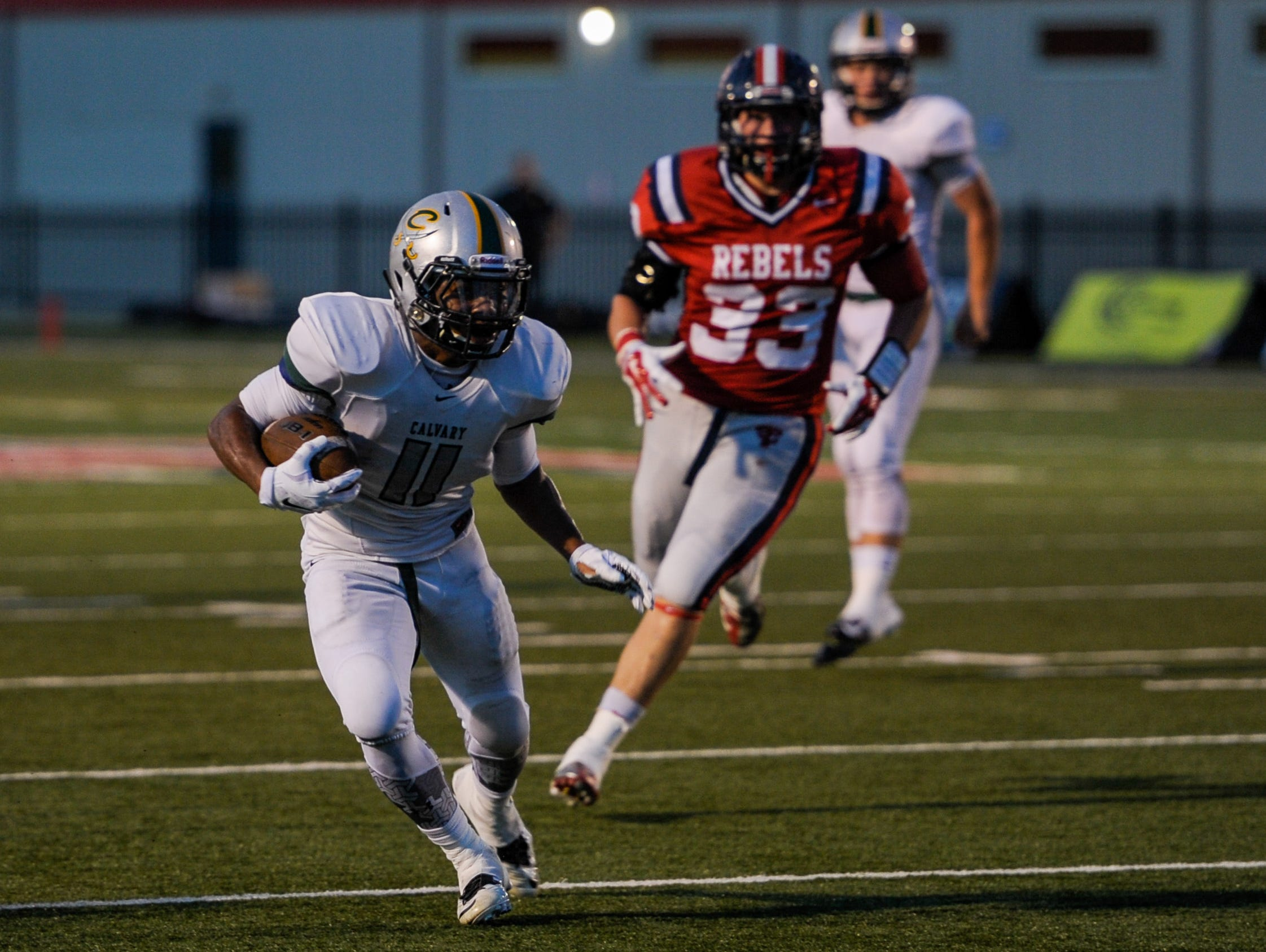 Calvary Baptist receiver Kyle Jones (11) runs with the football during the first half of an LHSAA football game at Teurlings Catholic High School in Lafayette, La., Friday, Sept. 4, 2015.
