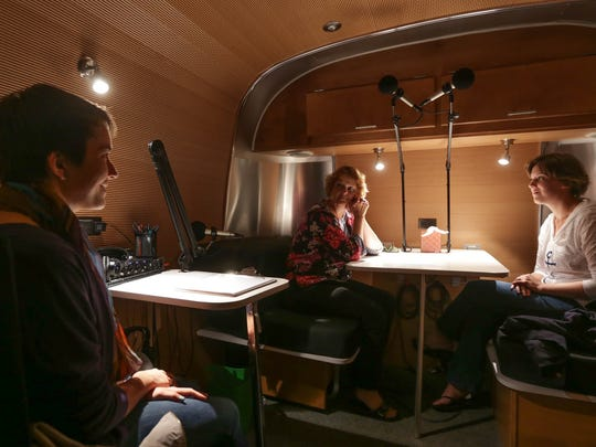 StoryCorps worker Vanessa Gonzalez-Block, left, 23, of New Jersey goes over tips before the recording process with Jill Kwiatkowski, 60, of Cheboygan and her daughter Abbey Hauswirth, 25, of Marquette in the soundproof section of the StoryCorps MobileBooth parked at the Peter White Public Library in Marquette on Sunday, July 27. Gonzalez-Block sat through the interview to monitor the recording process and help if needed to keep the conversation flowing.