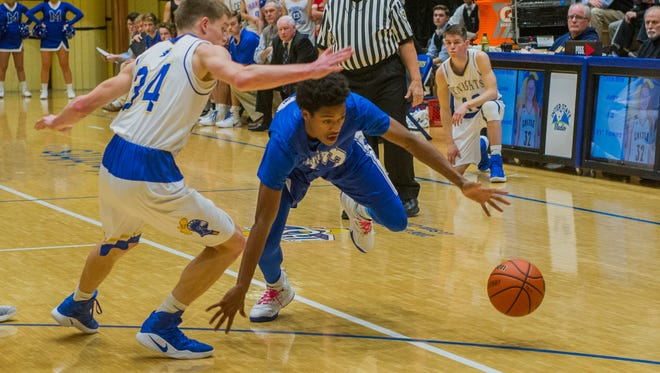 Castle's Noah McLean (34) and Memorial's Dylan Penn (13) go after a loose ball in the first quarter of their game at Castle High School in Newburgh, Friday, Jan. 6, 2017.