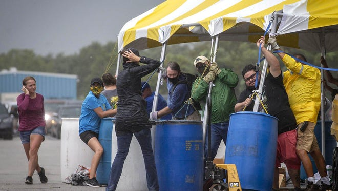 A strong storm front tests the strength of workers at the 20th Annual Sweet Corn Fiesta at the South Florida Fairgrounds on April 26, 2020. Gusts of wind threatened to blow away the tent where corn was being bagged before the fiesta was shut down due to concerns with the weather. The first truck of corn with 1000 crates were sold out in an hour and a half. A second truck arrived but the fiesta was shut down.