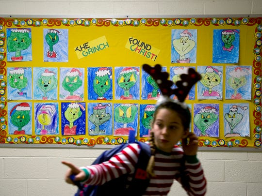 "A bulletin board is filled with students' rendering's of the Grinch at Holy Name School. The school is putting on a production of ""How the Grinch Found Christ in Christmas."""