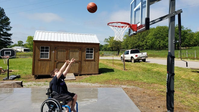 """Nate Jones of Scranton takes and makes his first shot on """"Nate's Court"""" recently. The Scranton community came together to build the 30 by 30 court for Jones. [Photo Courtesy Of Scranton Schools)"""